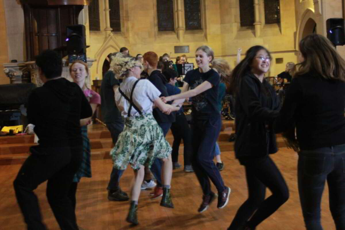 Some people dancing in a church in front of the band